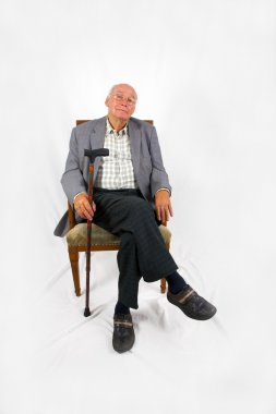 Old friendly man sitting in his armchair with walking stick
