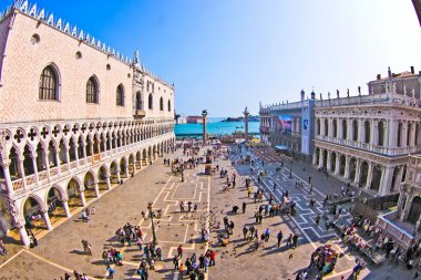 Tourists on San Marco square feed large flock of pigeons