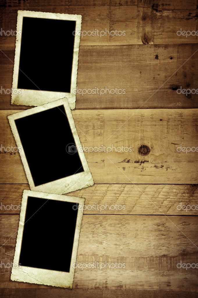 Old empty photo frames, over grunge wood background.