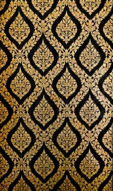 Golden Thai pattern on black wall