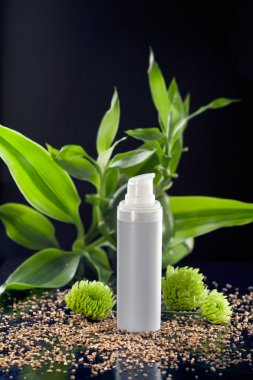Face cream moisturizer among bamboo leaves and flowers