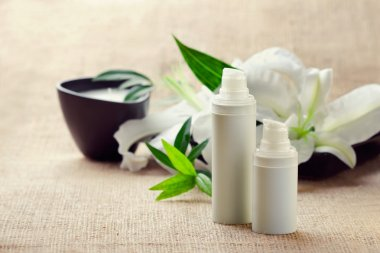 Face/body care concept: bottles of creams/lotions/serums with white lily flowers, closeup shot stock vector