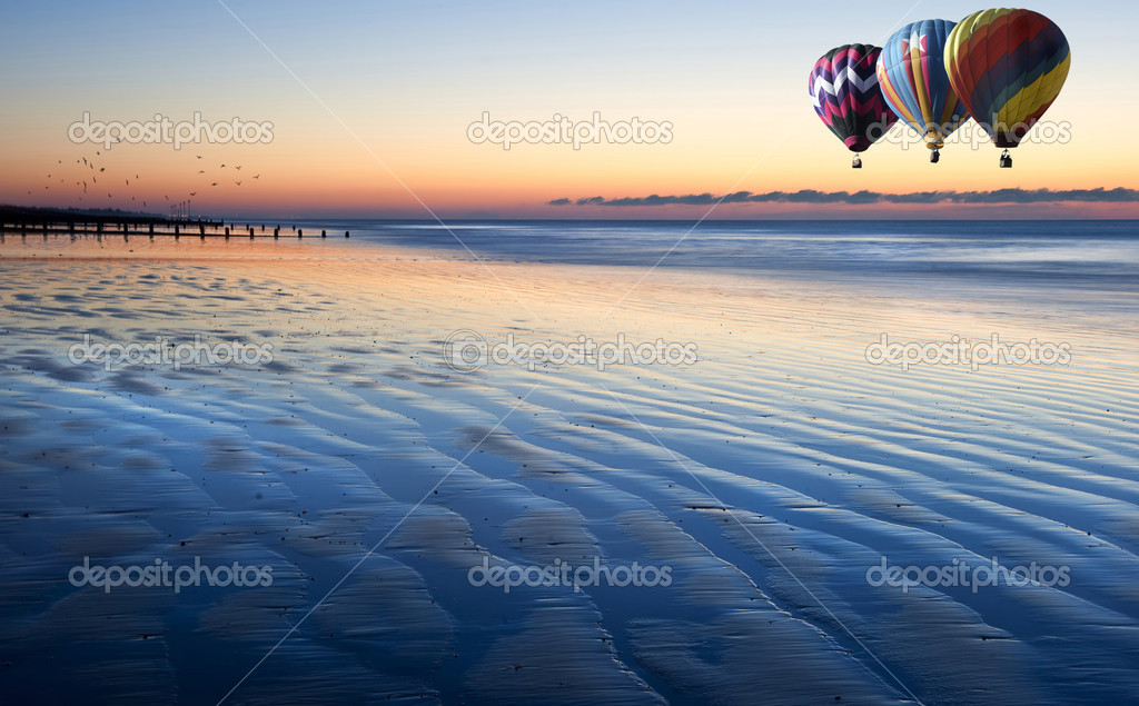 Hot air balloons over beautiful low tide beach vibrant sunrise