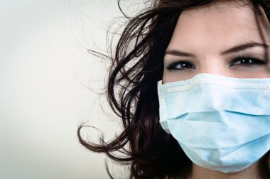 A girl in a protective mask against white isolated background