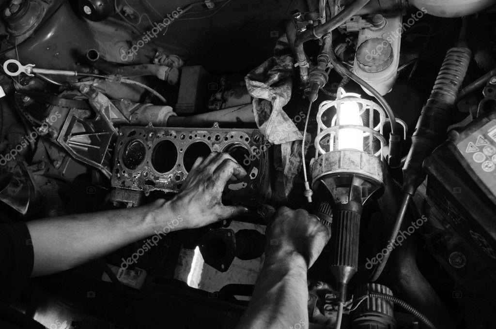 Hands of a worker repairing car