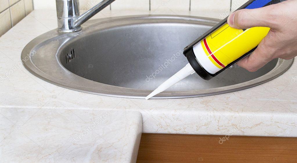 encanador colocando um selante de silicone para instalar uma pia de cozinha stock photo. Black Bedroom Furniture Sets. Home Design Ideas