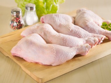 Fresh raw chicken legs arrangement on kitchen board