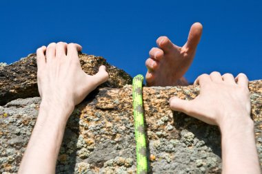 Rock climber reaching for helping-hand partner.