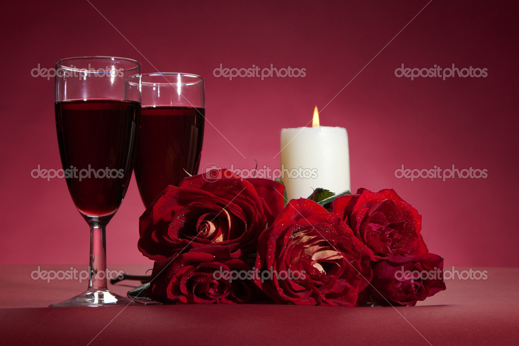 Bouquet of red roses, two glasses of wine and a candle on red background