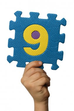 Children hand holding the number Nine. White isolated number