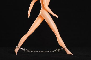 Toy women with metal chain on the legs