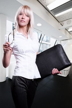 Young attractive blonde business women serious wearing glasses holding a folder in an office environment walking