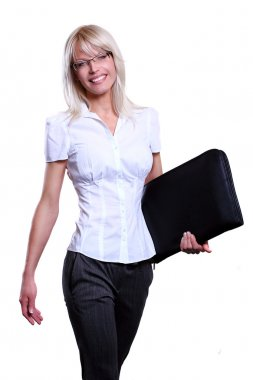 Young attractive business women smiling wearing glasses holding a folder in an office environment walking