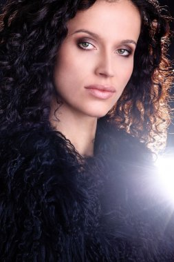 Glamour beautiful brunette fashion model with curly hair and green eyes, smoky make up, a light flare on the back ground
