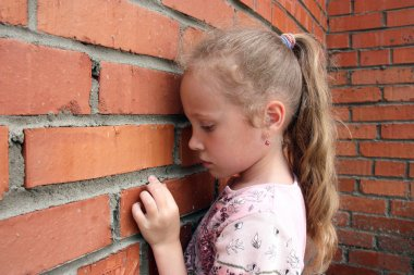 Sad child with a brick wall