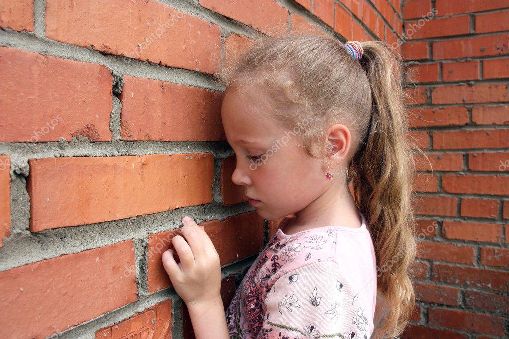 Sad child with a brick wall