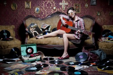 Girl playing guitar on an old sofa