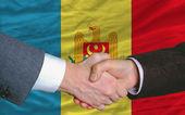 Fotografia stretta di mano di uomini daffari dopo buon affare davanti alla bandiera della Moldavia