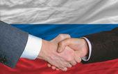 Fotografie Businessmen handshake after good deal in front of russia flag