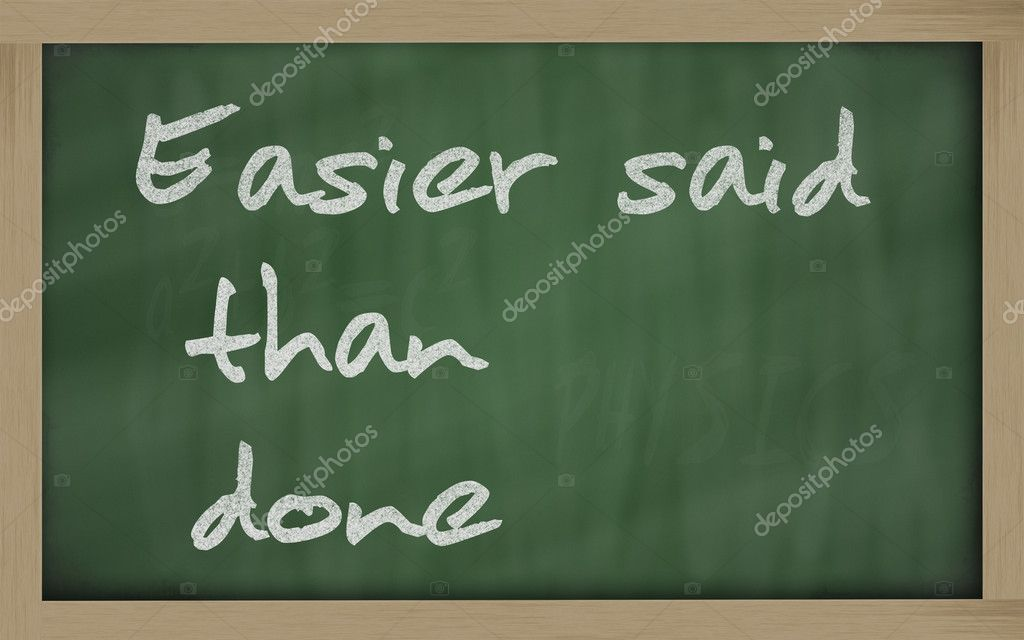 easier said than done written on a blackboard foto de stock