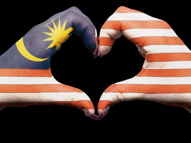 Heart and love gesture by hands colored in malaysia flag for tou