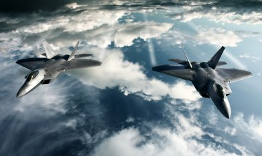 Two F-22 Raptors in high attitude above the clouds