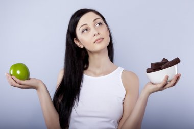 Young woman holding apple and chocolates