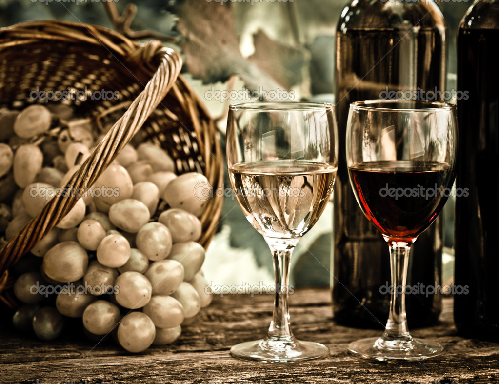 Wine bottles, two glasses and grapes in basket