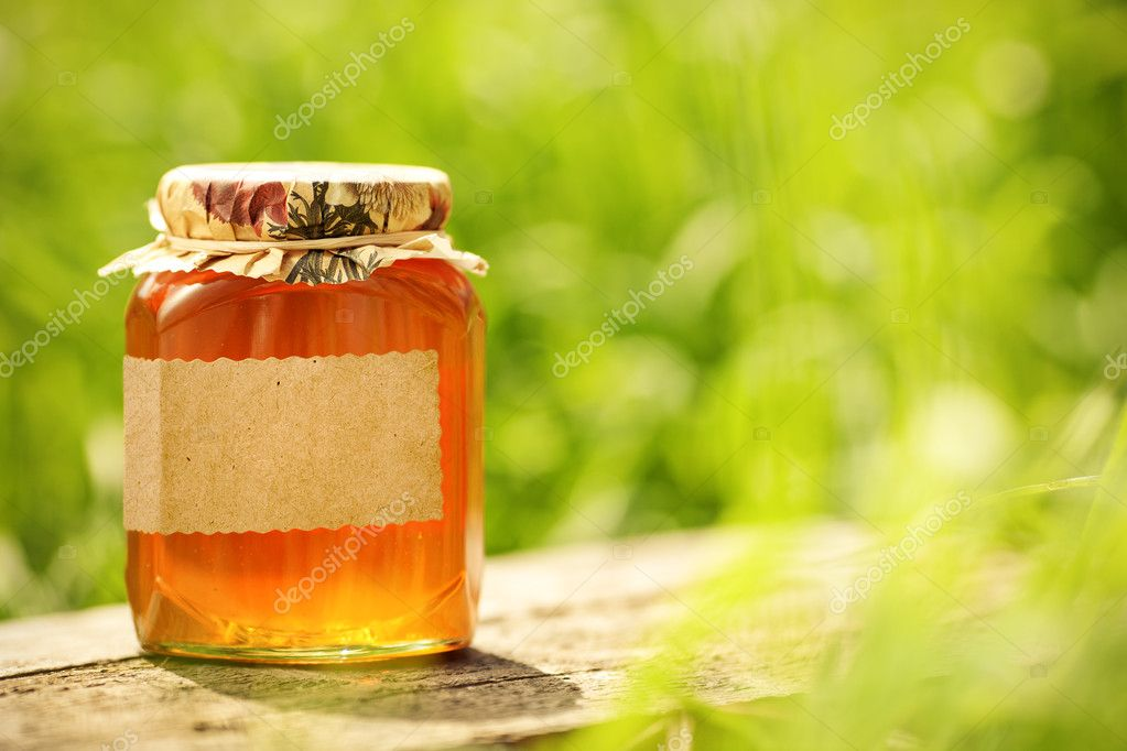 Flowery honey with blank label in glass jar