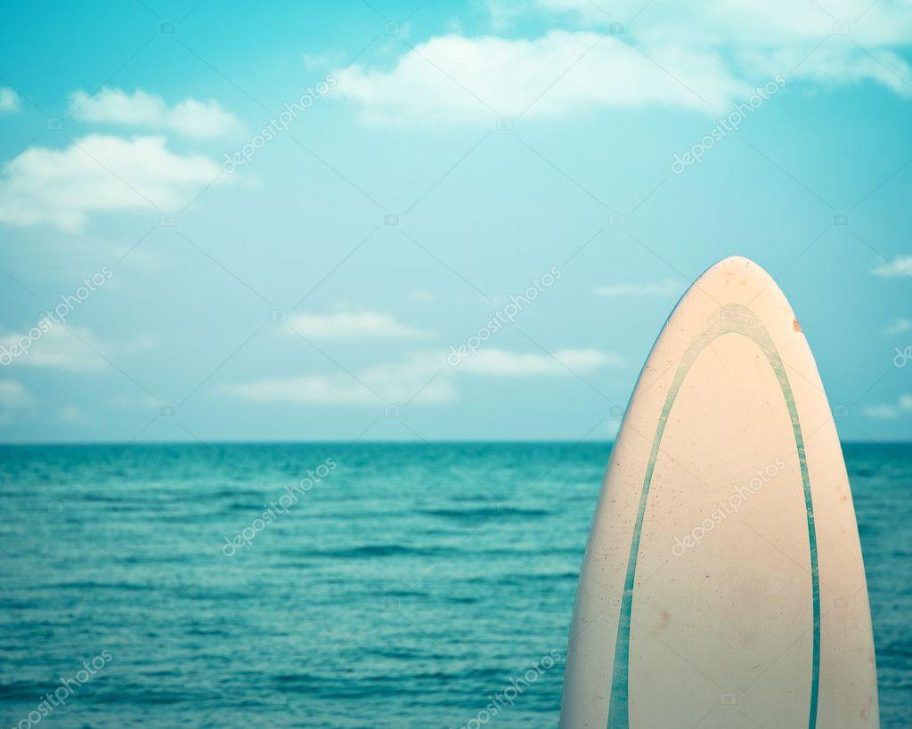Old grunge surfboard against calm sea. Retro toned image