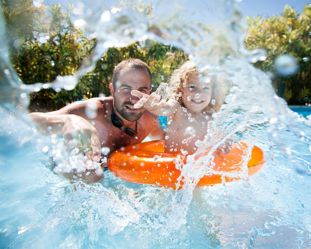 Happy family playing in blue water of swimming pool on a tropical resort at the sea. Focus on children`s hand and splash, shot was taken with waterproof box stock vector