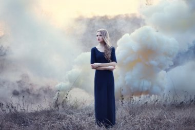 Sensual beautiful girl in smoke on natur