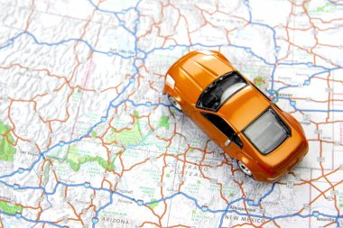 Orange sports car toy on map
