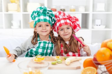 Little chefs slicing fruits in the kitchen