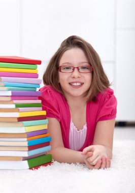Young girl with lots of books