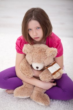 Sad young girl sitting with teddy bear