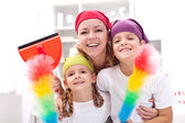 Fotografie Cleaning taskforce - woman with kids tidy up