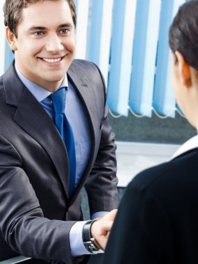 Two businesspeople or businessman and client handshaking