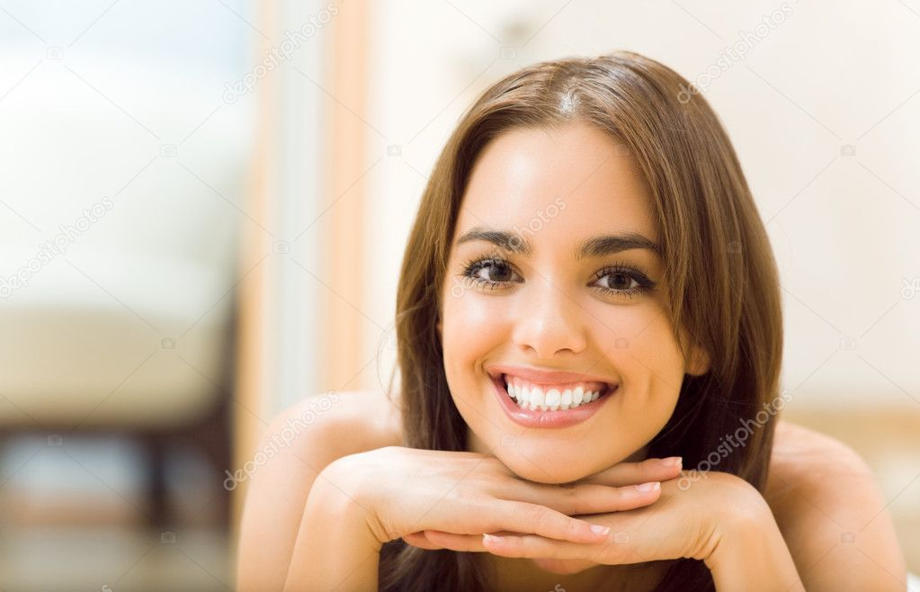 Portrait of young smiling woman, at home