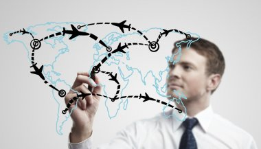 Young business man drawing an airplane routes on world map