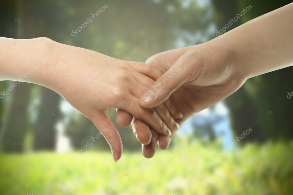 Couple hands closed together outdoors.