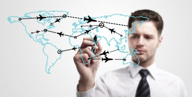 Young business man drawing an airplane routes on world map.