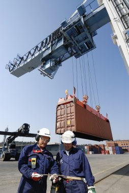 Dock workers, truck and container crane