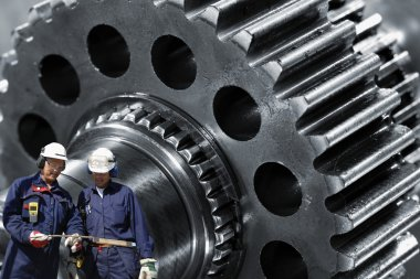 Metal workers with giant machinery