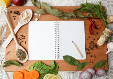 Notebook for recipes and spices on wooden board