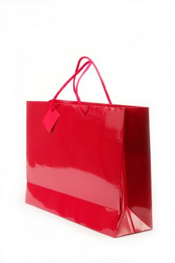 Red gift bag in the women's hands on a white background.