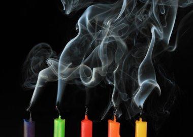 Five color extinguished candles on black background