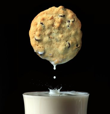Fresh baked chocolate chip cookie being dipped into a fresh glass of milk