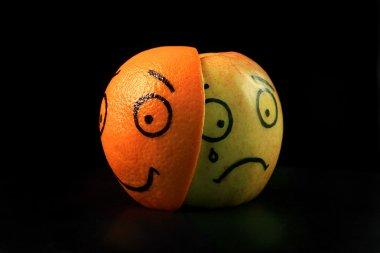 Sad apple with happy orange mask