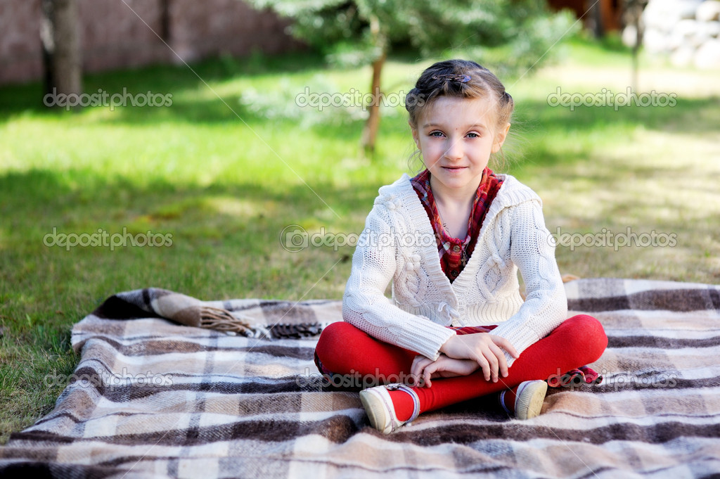 Child girl sitting on plaid in a garden